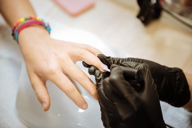 Hora da manicure. perto de uma unha artista profissional usando luvas pretas fazendo manicure para adolescente