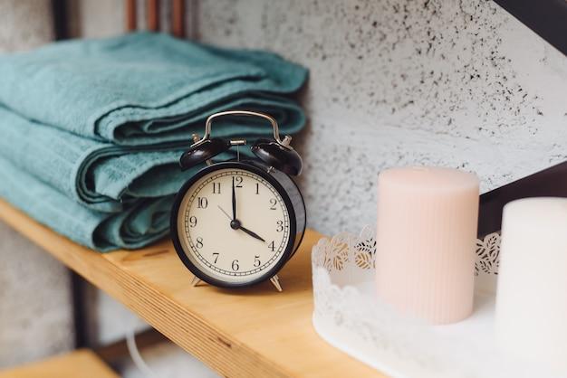 Hora da massagem relógio preto analógico em uma prateleira com toalhas azuis e velas de cera. o conceito de itens de massagem