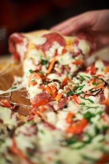 Hora da refeição na pizzaria, homem tomando uma fatia da pizza tiro com muito fina profundidade de campo. quadro, armação. entregue a fatia de pizza cortada e leve-a, fim acima, tiro macro. pizza e fatia de pizza na mão