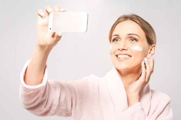 Hora da selfie! retrato de uma jovem mulher bonita sorrindo enquanto toma um creme facial, isolado no fundo branco, com espaço de cópia.