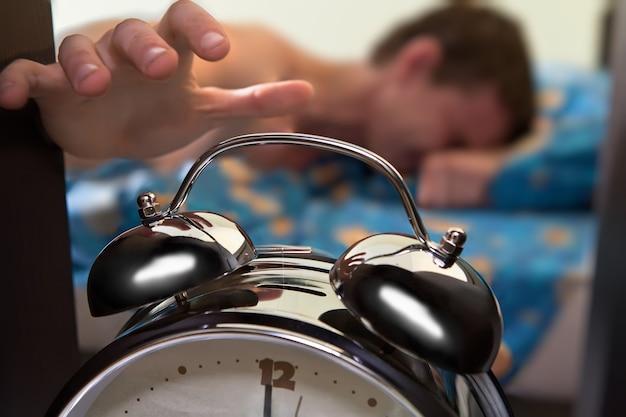 Hora de acordar despertador e homem preguiçoso