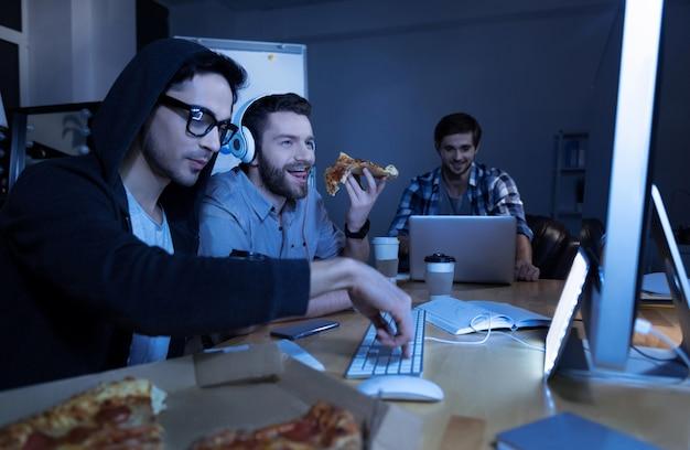 Hora de comer. homem alegre e feliz segurando uma fatia de pizza e comendo enquanto olha para a tela do computador