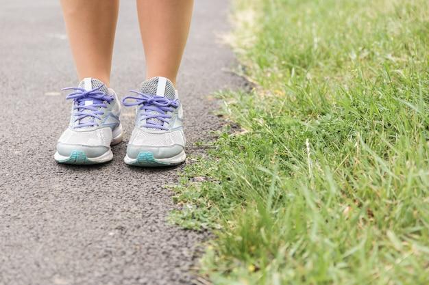 Hora de correr. close-up vista das pernas da mulher e calçados esportivos no asfalto pronto para começar a correr