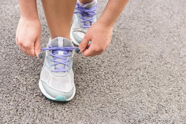 Hora de correr. closeup vista da mulher amarrar cadarços no asfalto