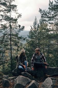 Hora de descansar. lindo casal jovem sentado nas rochas e sorrindo enquanto caminham juntos na floresta