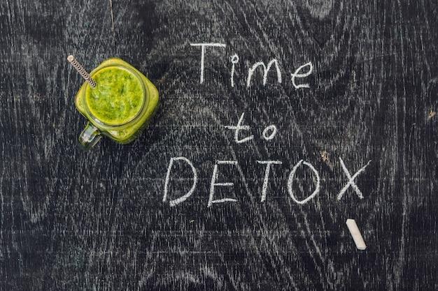 Hora de desintoxicar a inscrição de giz na mesa de madeira e smoothies verdes feitos de espinafre. conceito de alimentação e esportes saudável.