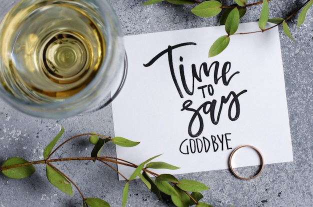Hora de dizer adeus. a inscrição em uma folha de papel branco. vinho branco em um copo de vidro. anel de noivado de ouro.