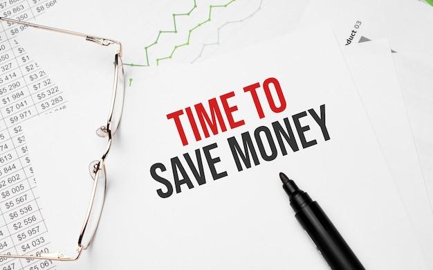 Hora de economizar dinheiro escrevendo com gráfico, papéis, caneta e óculos