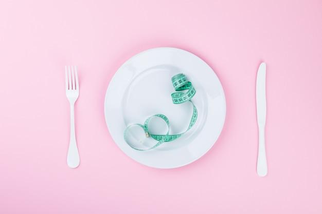Hora de emagrecer. fita métrica com indicadores em forma de centímetros no prato branco