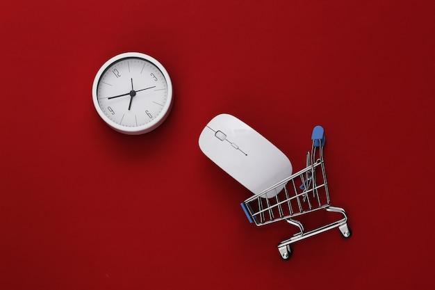 Hora de fazer compras. mouse do pc e mini carrinho de compras com relógio sobre fundo vermelho. vista do topo. postura plana