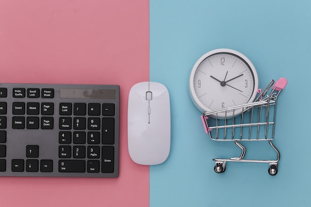 Hora de fazer compras. supermercado online. teclado de pc e carrinho de compras com relógio em rosa azul pastel