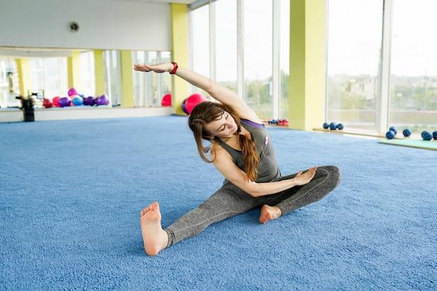 Hora de ioga. mulher jovem e atraente exercitando e sentado no chão no ginásio