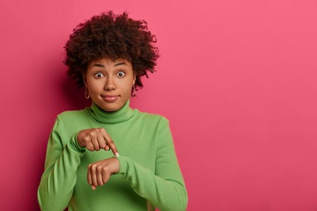 Hora de ir, se apresse! mulher étnica chocada aponta para o pulso, faz gestos de tempo, mostra que devemos fazer tudo rapidamente