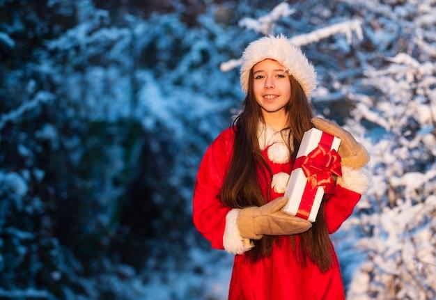 Hora de milagres. pai natal generoso. criança feliz garota ao ar livre natureza nevada. feliz natal. conceito de infância feliz. felicidade e alegria. chapéu de papai noel de criança. presentes do papai noel. manhã gelada de natal.