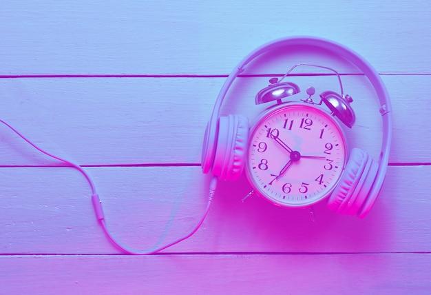 Hora de ouvir o conceito de música com despertador retrô e fones de ouvido