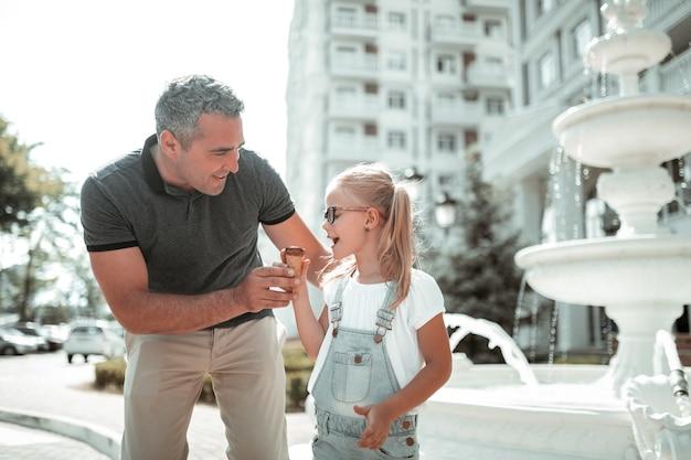 Hora de pai e filha. menina feliz comendo sorvete de chocolate andando com seu pai sorridente e abraçando-a.