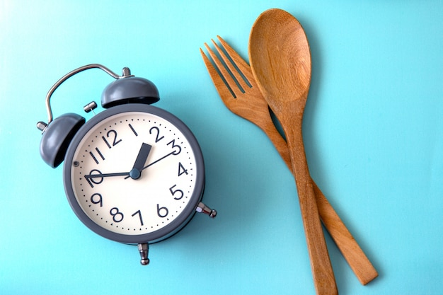 Hora de perder peso, comer controle ou tempo para dieta conceito, despertador com uma decoração de conceito de ferramenta saudável sobre fundo azul