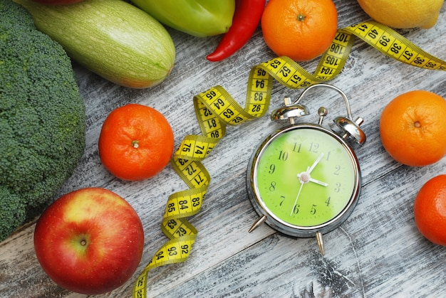 Hora de perder peso. frutas, legumes e despertador. fazendo dieta.