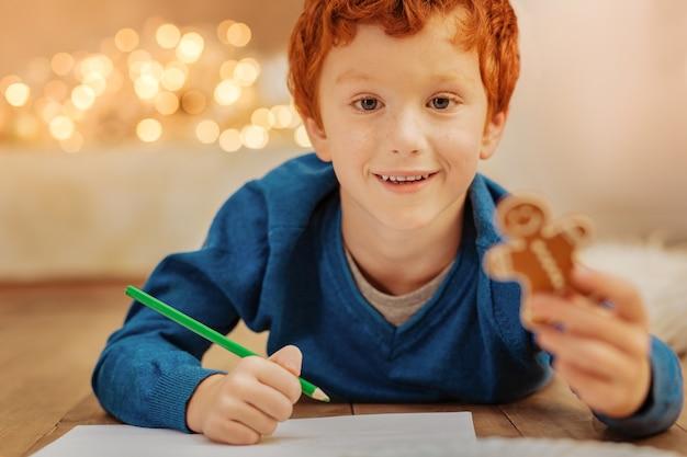 Hora de relaxar. garoto ruivo radiante de empolgação, deitado no chão e desenhando com lápis coloridos.