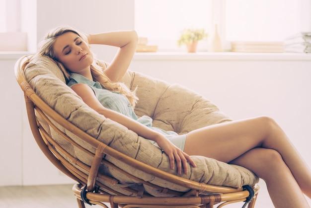 Hora de relaxar. mulher jovem e bonita mantendo os olhos fechados e segurando a mão atrás da cabeça enquanto está sentada em uma cadeira grande e confortável em casa