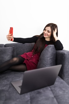 Hora de selfie. mulher jovem e bonita fazendo selfie com sorriso enquanto está sentado no sofá com o laptop de joelhos no interior de casa