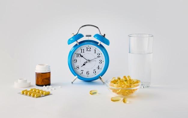 Hora de tomar seus comprimidos um despertador em um fundo branco mostra a hora de tomar a medicação