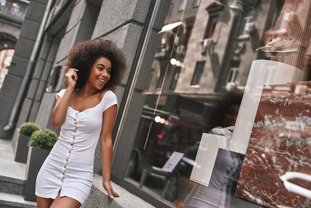 Hora de trocar de roupa jovem brincalhão afro-americana em um vestido branco sexy sorrindo e