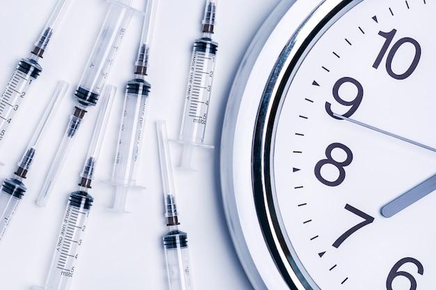Hora de vacinar conceito. seringas de vacina e despertador