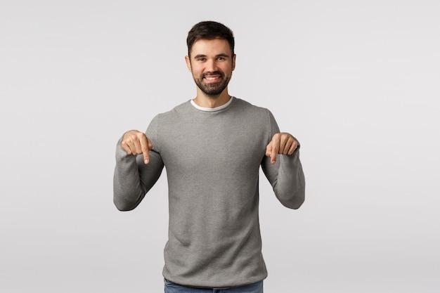 Hora de ver, veja aqui. feliz, carismático homem barbudo sorridente e simpático, de suéter cinza, convide um evento, compartilhe um link, discuta uma oferta promocional, apontando para baixo para promover o produto,