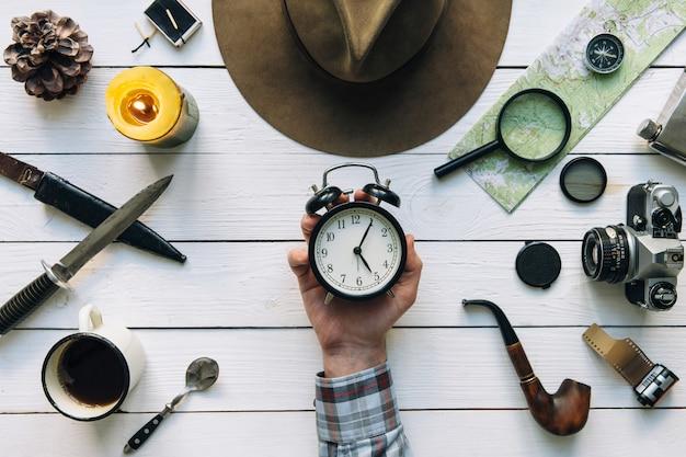 Hora de viajar com a mão explorador segurando o despertador vintage