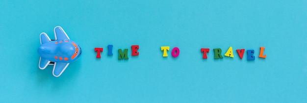 Hora de viajar e avião de brinquedo engraçado infantil em fundo de papel azul