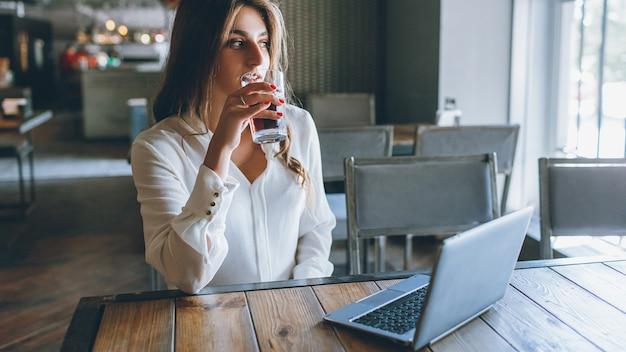 Hora do almoço. pausa do dia útil. mulher de negócios relaxado, desfrutando de uma bebida gelada no café moderno do sotão.