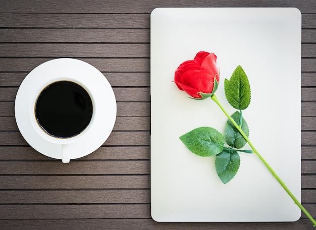 Hora do café com laptop, xícara de café, rosa vermelha