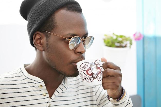 Hora do café. confiante na moda masculina africana no chapéu e óculos escuros segurando a caneca, bebendo cappuccino fresco, olhando à frente com expressão pensativa, desfrutando de uma bebida quente durante o almoço no café