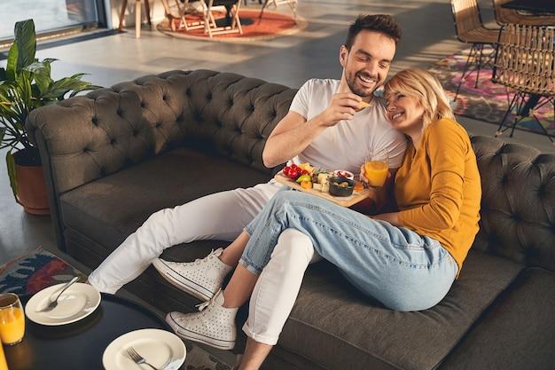 Hora do café da manhã. homem bonito e carinhoso alimentando sua adorável jovem esposa com um pedaço de queijo