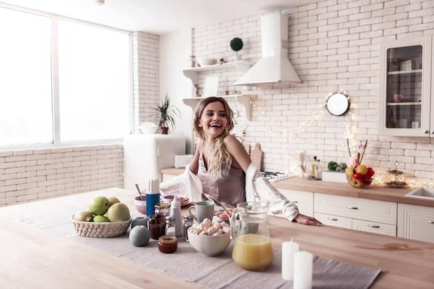 Hora do café da manhã. mulher jovem e bonita de cabelos compridos vestindo um top de cetim e seu marido moreno cozinhando o café da manhã juntos