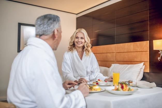 Hora do café da manhã. um casal com vestes brancas tomando café da manhã e parecendo satisfeito