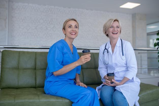 Hora do café. duas médicas sentadas no sofá, tomando café