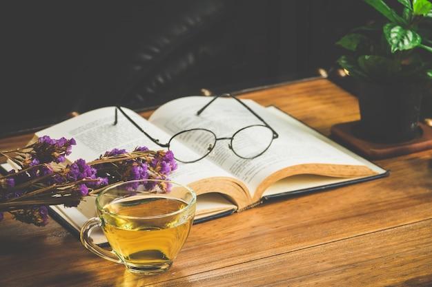 Hora do chá com a leitura de livro na mesa no café