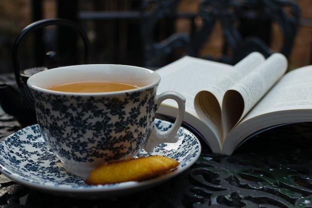 Hora do chá relaxante e leitura na varanda em uma mesa de ferro. livro do dia mundial