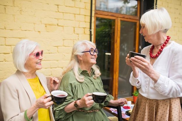 Hora do chá. senhoras se sentindo bem enquanto passam um tempo juntas e tomando chá