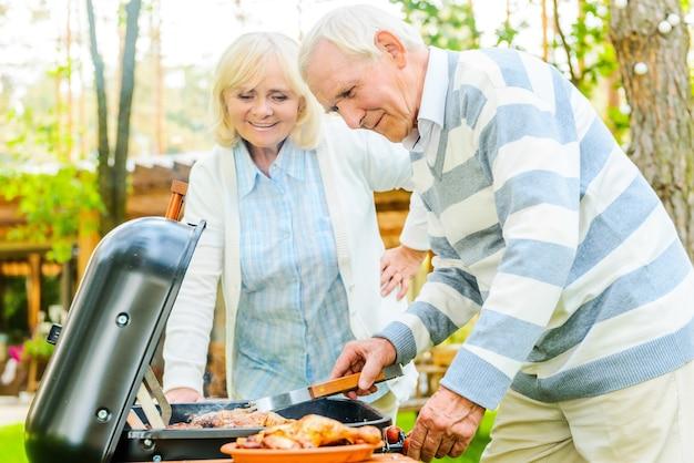 Hora do churrasco. casal feliz sênior fazendo churrasco de carne na grelha enquanto está de pé no quintal de sua casa