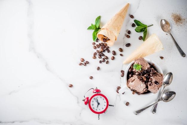Hora do conceito de café, com um despertador por horas no quadro. sorvete caseiro de café, servido com grãos de café e folhas de hortelã, com casquinhas de sorvete, colheres. fundo de mármore branco, acima