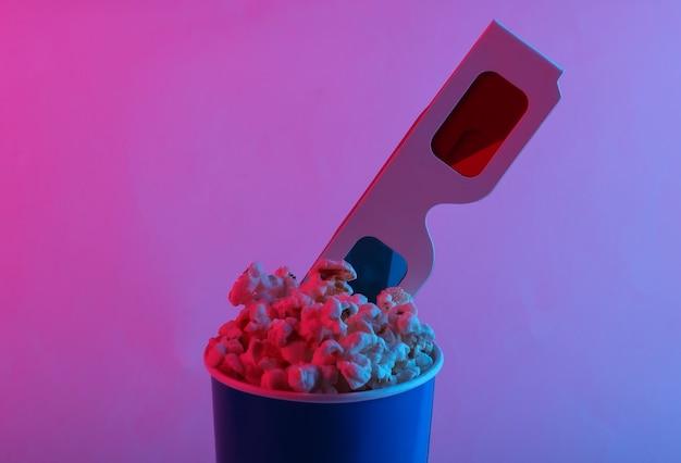 Hora do filme balde de papelão de pipoca com óculos 3d descartáveis de papel anáglifo estereoscópico em luz de néon gradiente rosa azul
