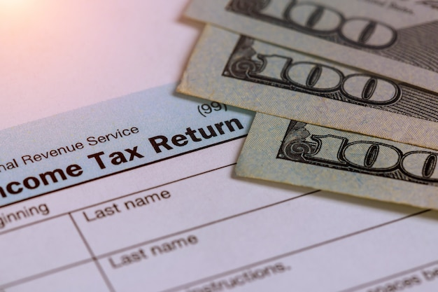 Hora do imposto closeup de 1040 retorno de imposto dos eua com 100 notas