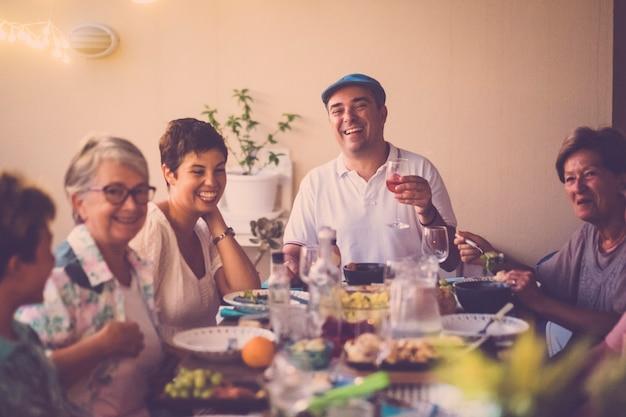 Hora do jantar com mesa comprida cheia de comidas e bebidas variadas