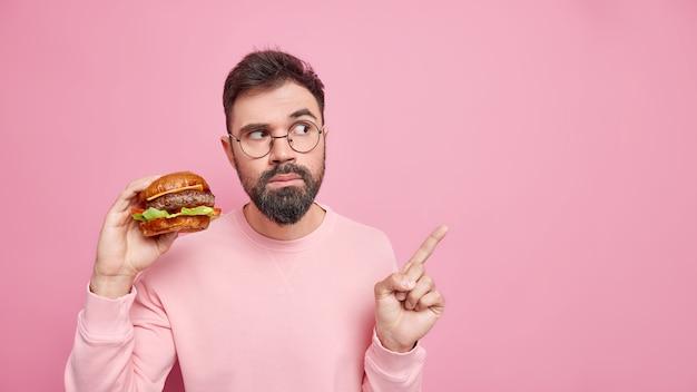 Hora do lanche. homem adulto barbudo sério segurando hambúrguer delicioso e comendo pratos de trapaça no espaço em branco usa óculos redondos roupas casuais