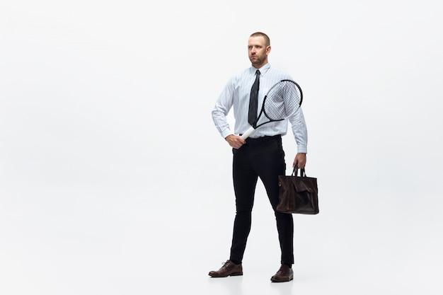 Hora do movimento. o homem na roupa do escritório joga o tênis isolado no branco. empresário treinando em movimento, ação. olhar incomum para desportista, nova atividade. esporte, estilo de vida saudável.