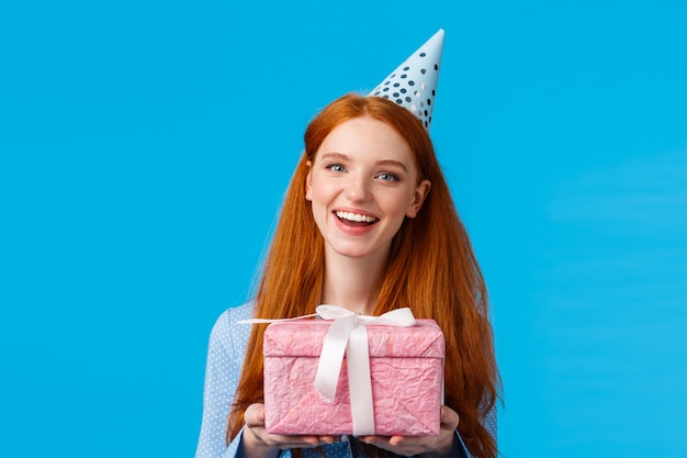 Hora do presente. ruiva alegre adolescente, universitária, comemorando seu aniversário, segurando o presente embrulhado rosa fofo e usando chapéu de aniversário, sorrindo alegremente em pé fundo azul