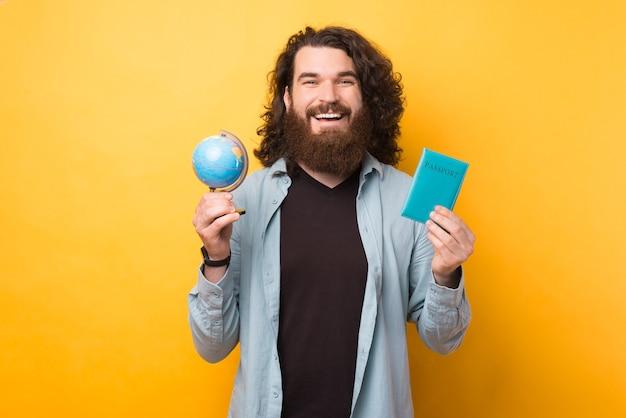Hora perfeita para viajar pelo mundo, alegre homem barbudo hipster segurando um globo e um passaporte sobre fundo amarelo